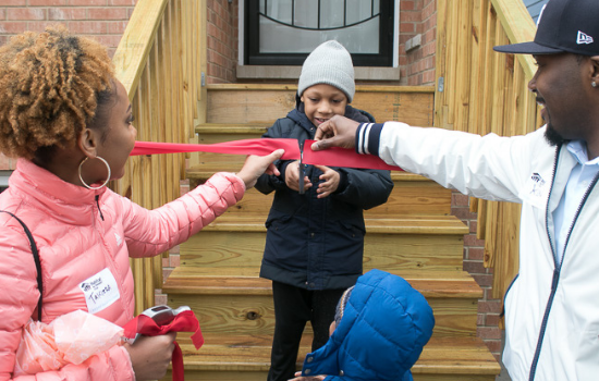 Family cutting the ribbon on their affordable Habitat home!