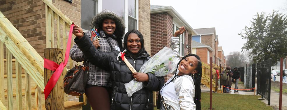 Three women celebrate their Habitat Chicago home dedication